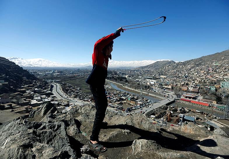 Кабул, Афганистан. Мальчик с рогаткой на холме