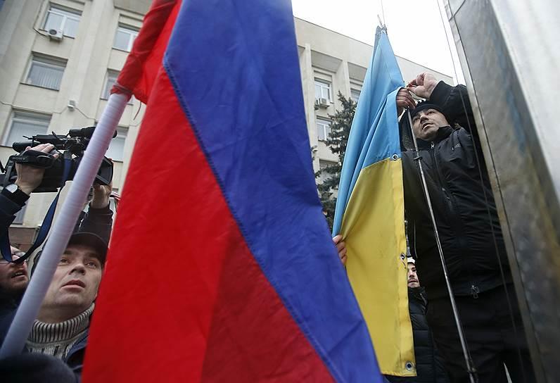 27 февраля две группы вооруженных людей в камуфляже без опознавательных знаков вывели из здания Верховного совета и Совета министров Крыма дежуривших там милиционеров. Над зданиями были подняты российские флаги