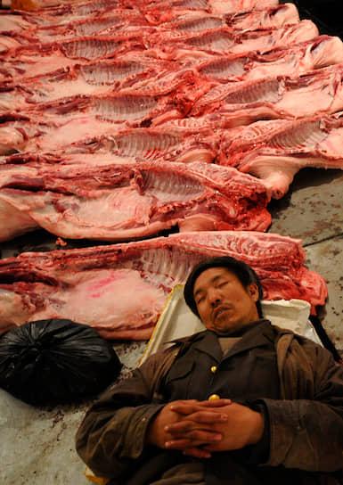 Продавец мяса на оптовом рынке свинины в Китае, 2008 год