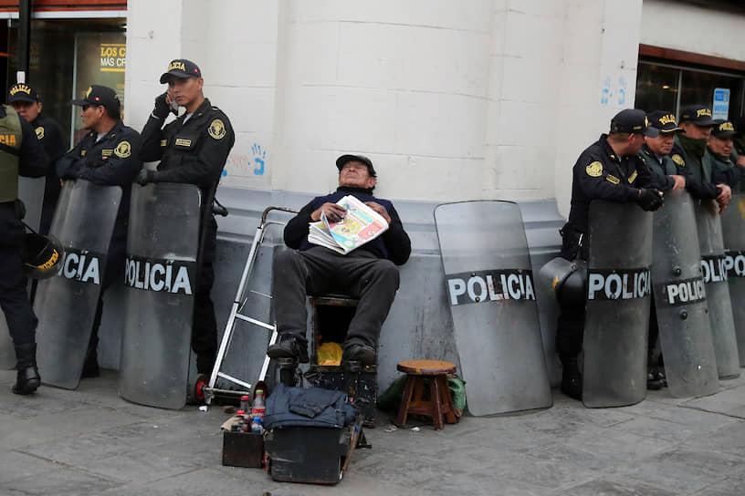 Чистильщик обуви в столице Перу во время акции протеста против коррупции, 2018 год