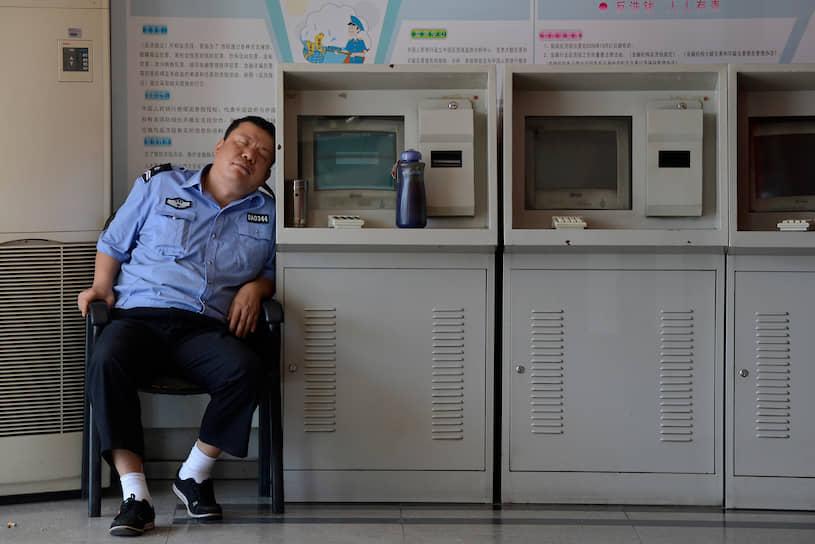 Охранник рядом с торговыми автоматами в китайском Тайюане, 2012 год
