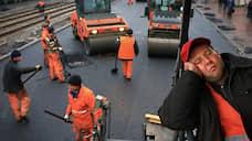 Рабочий во время укладки асфальта на одной из улиц Москвы, 2011 год