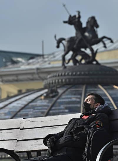Молодой человек отдыхает на скамье на Манежной площади, 2020 год