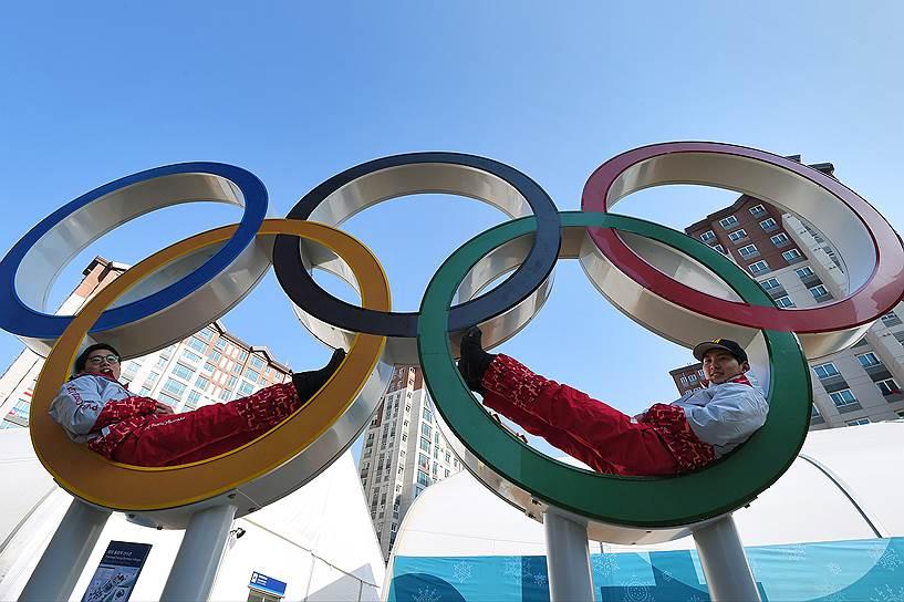 Спортсмены фотографируются на фоне стеллы с пятью олимпийским кольцами в Олимпийской деревне