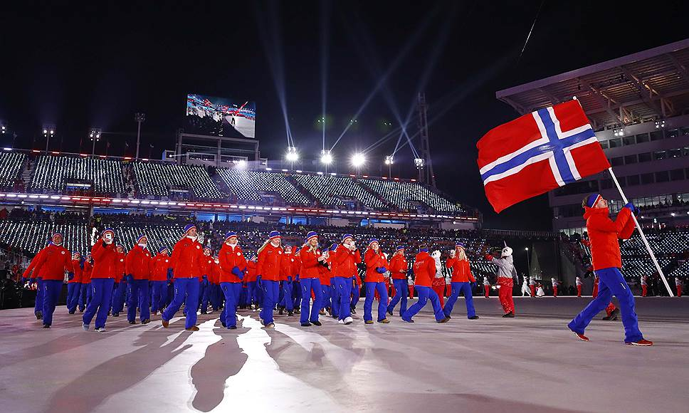 Биатлонист Эмиль Хегле Свендсен несет флаг Норвегии на церемонии открытия Олимпиады
