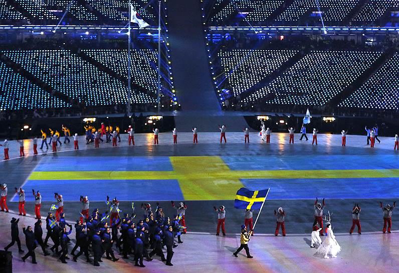 Кёрлингист Никлас Эдин несет флаг Швеции