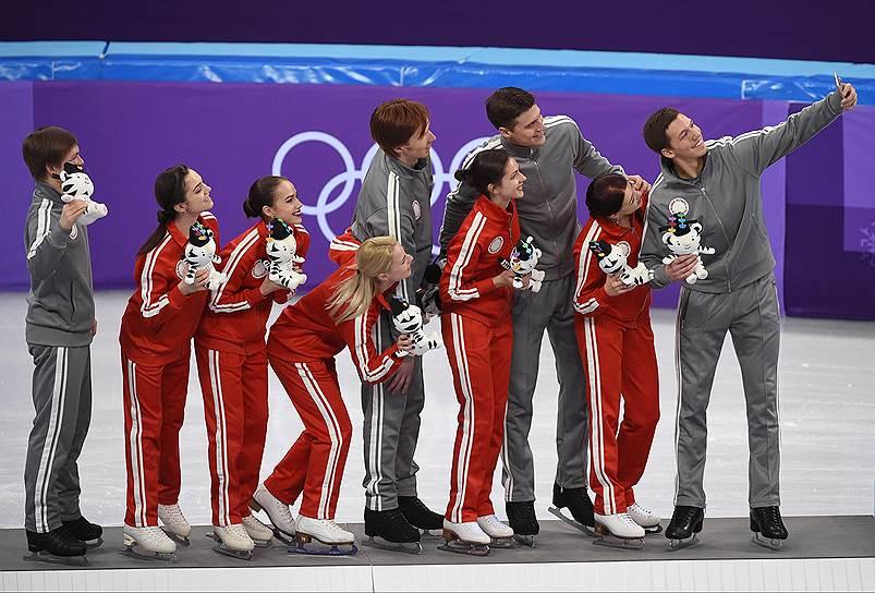Олимпийские спортсмены из России, завоевавшие серебряные медали в командных соревнованиях по фигурному катанию, во время цветочной церемонии награждения