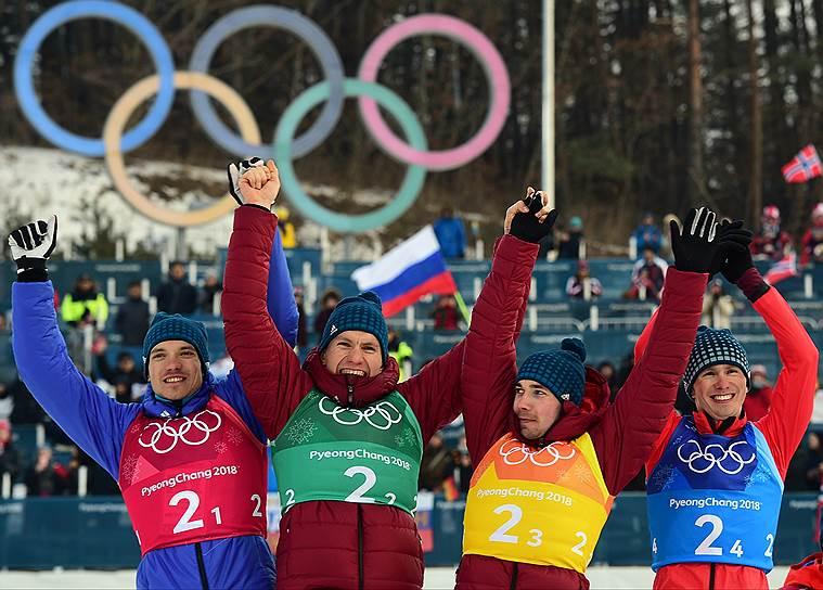 Слева направо: российские лыжники Андрей Ларьков, Александр Большунов, Алексей Червоткин и Денис Спицов во время церемонии награждения победителей с серебряными медалями