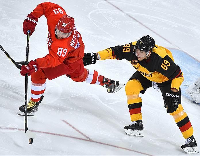 Игрок сборной Германии Давид Вольф (справа) и игрок команды ОСР Никита Нестеров (слева) во время финального матча по хоккею среди мужчин между сборной Германии и командой Олимпийских спортсменов из России