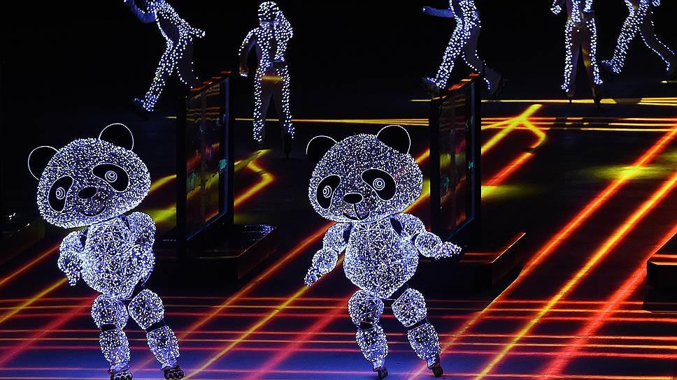 В ходе церемонии закрытия в центр сцены поднялись фигуры в костюмах медведей и дети с огоньками в руках