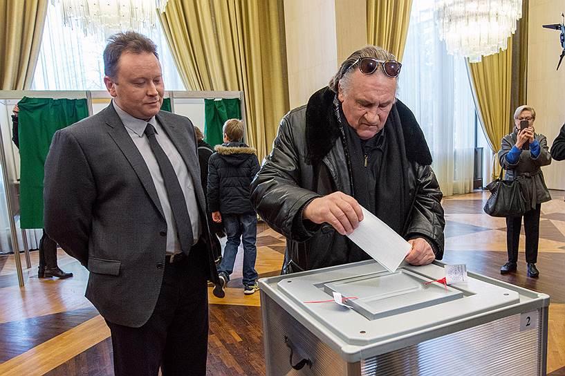 Французский актер Жерар Депардье (справа), получивший российское гражданство в 2013 году, во время голосования на выборах президента РФ в посольстве России во Франции