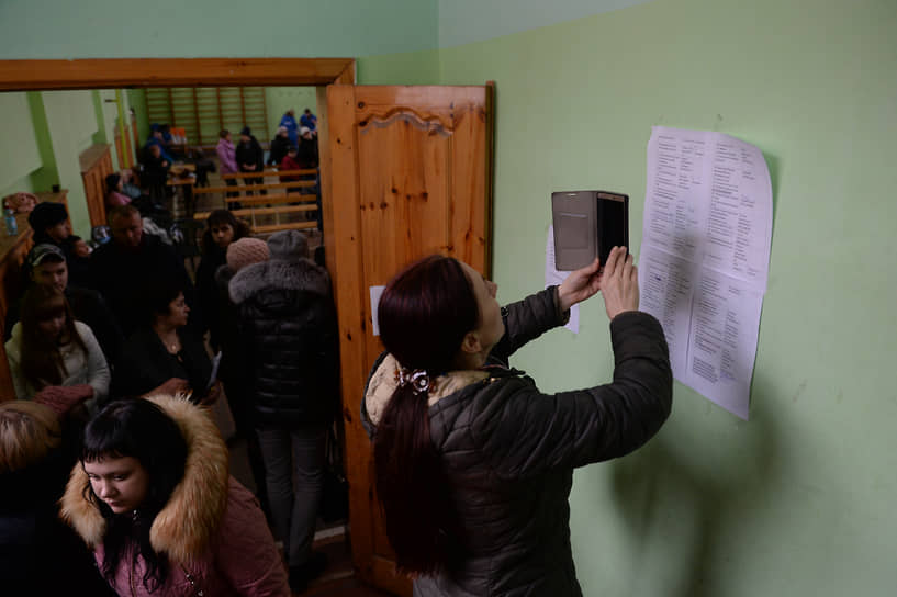 Женщина фотографирует на мобильный телефон списки пропавших без вести при пожаре в торговом центре 26 марта