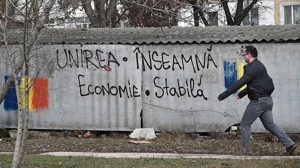 Надпись на заборе: «Объединение означает стабильную экономику»