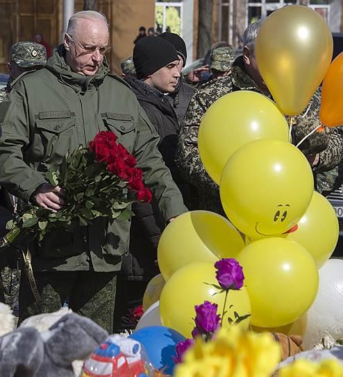 Председатель Следственного комитета России Александр Бастрыкин (в центре) во время посещения стихийного мемориала из цветов и игрушек в память о жертвах пожара в торговом центре