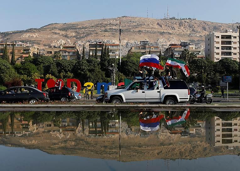 Сирийцы с российскими и сирийскими флагами во время акции протеста против авиаударов США в Дамаске