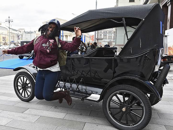 Девушка фотографируется с ретро-автомобилем