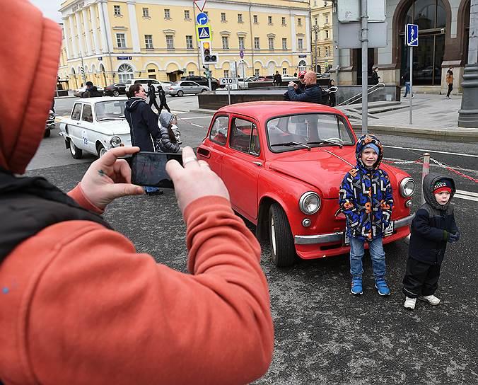 Дети фотографируются рядом с красным ретро-автомобилем