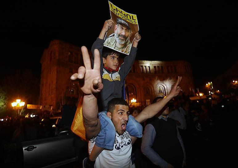 Митингующий держит в руках плакат с изображением лидера оппозиционного движения «Елк» Никола Пашиняна