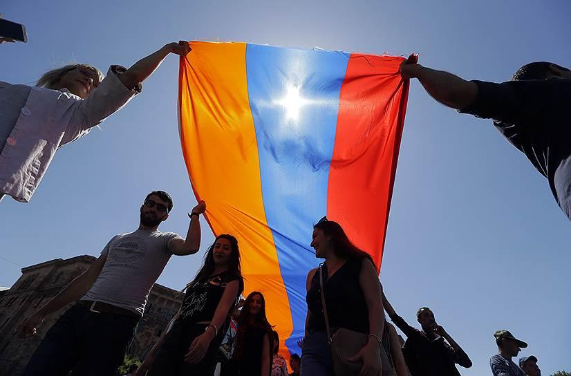 Протестующие несут в руках армянский флаг