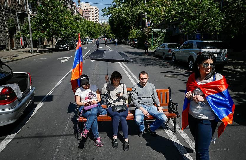 Протестующие сидят на скамейке, блокируя проезжую часть