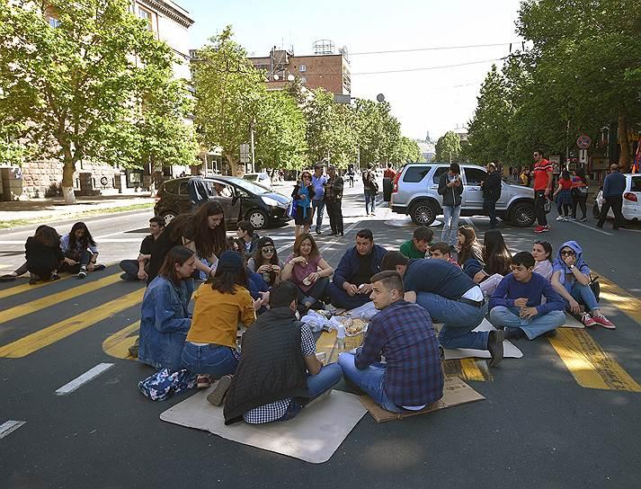 Протестующие сидят на проезжей части, блокируя дорогу