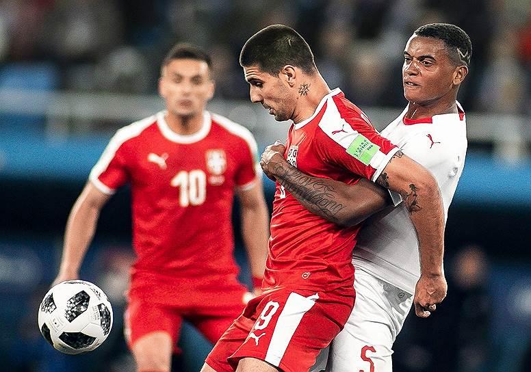 Матч между сборными Сербии и Швейцарии на стадионе «Калининград». Сербский игрок Александр Митрович (в центре) борется за мяч со швейцарцем Мануэлем Аканджи (справа)