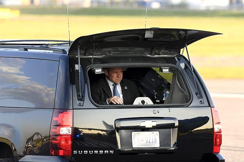 Сотрудник службы безопасности президента США Дональда Трампа осматривает территорию аэропорта