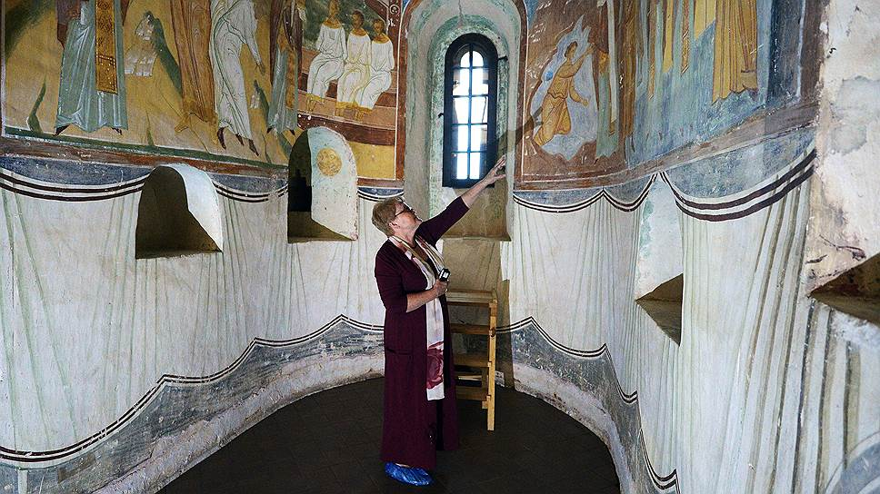 Хранитель собора Елена Шелкова показывает на фресках места, где таяние инея привело к подтекам.