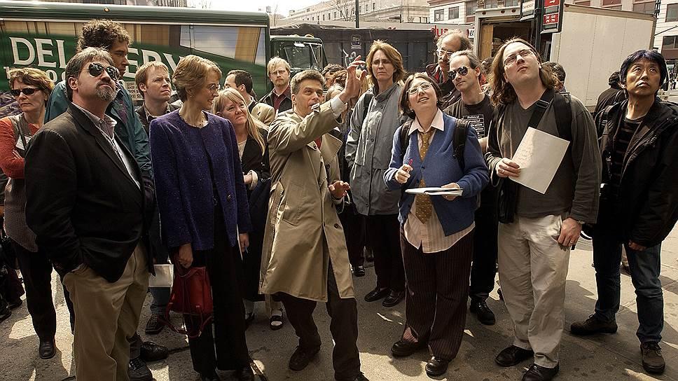 Билл Браун (в центре) указывает на камеры видеонаблюдения во время пешеходной экскурсии, проводимой Surveillance Camera Players, 3 апреля 2003 года