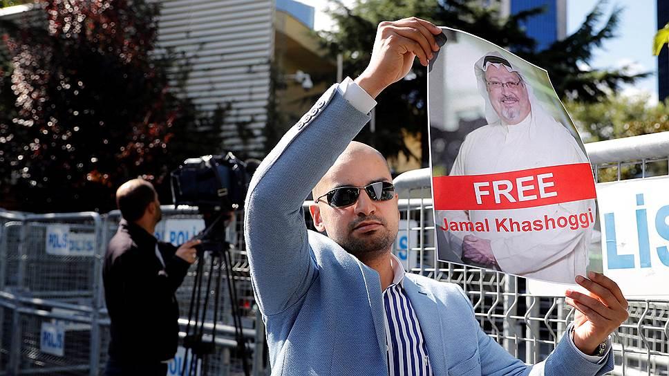 Участник демонстрации держит фотографию журналиста Джамаля Хашогги напротив здания консульства Саудовской Аравии в Стамбуле, Турция