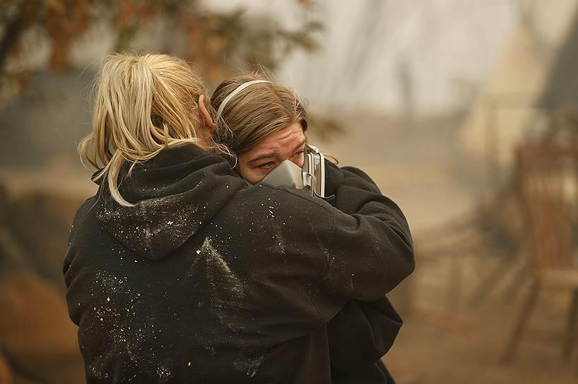 Местная жительница Кристин Харви (слева) утешает свою дочь Арайю у остатков их сгоревшего дома