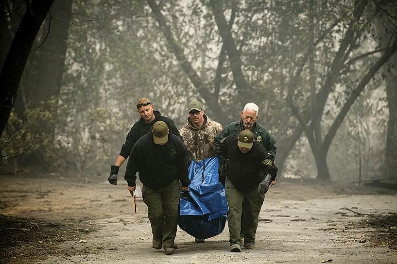 Заместители шерифа переносят останки погибших при пожаре