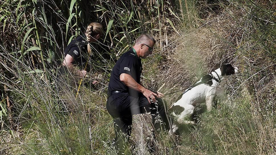 Детективы Скотленд-Ярда с собакой-ищейкой исследуют участок побережья Прая-да-Луш в Португалии