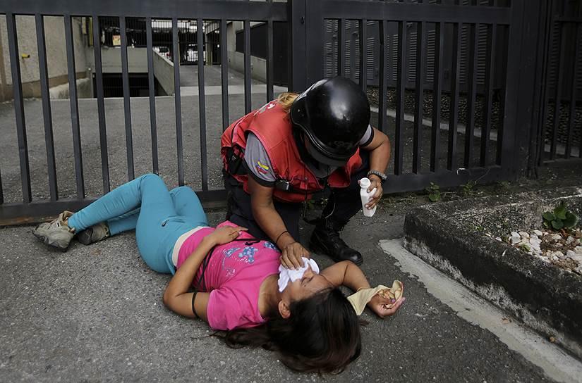 Женщине, пострадавшей от распыления слезоточивого газа в Каракасе, оказывают помощь