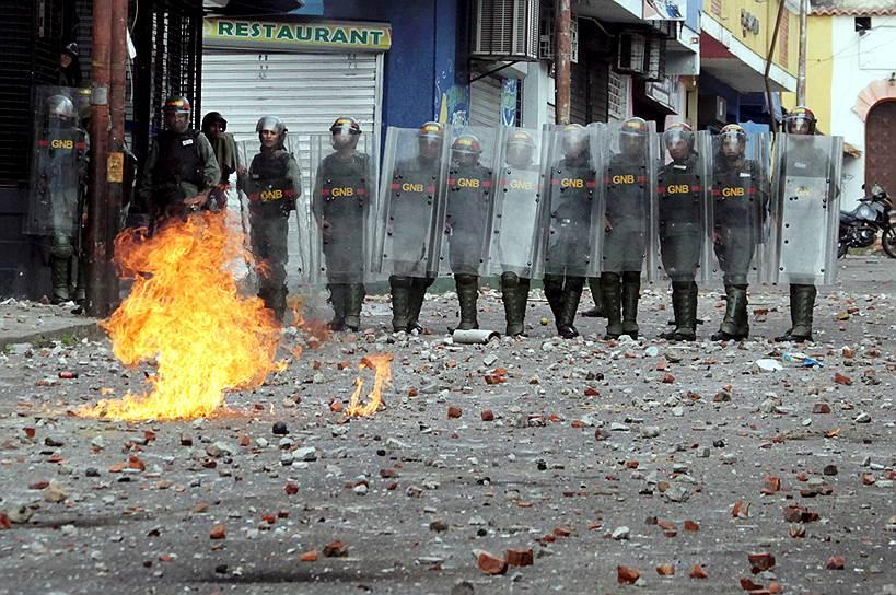 Полицейские во время столкновений с оппозиционерами в Каракасе