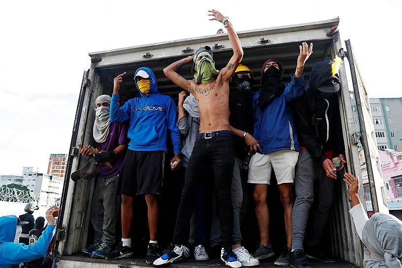 Демонстранты на грузовике во время акции протеста в Каракасе