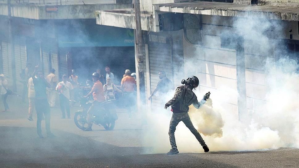 Демонстрант кидает обратно полиции шашку со слезоточивым газом в Тачире на западе Венесуэлы