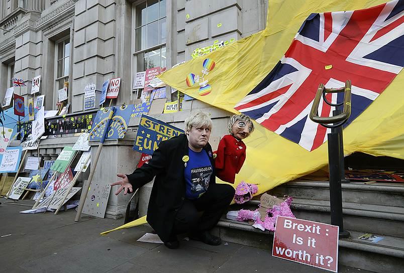 Демонстрант, похожий на Бориса Джонсона, держит марионетку в виде премьер-министра Терезы Мэй