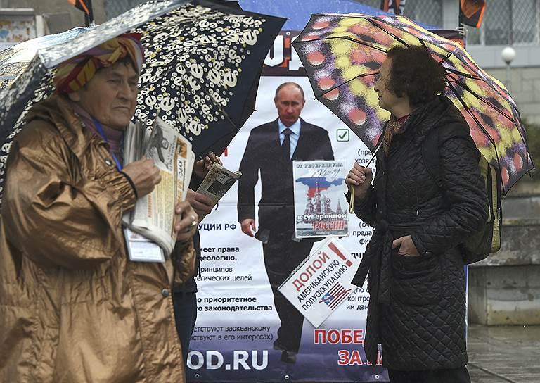 12 апреля, Ялта. Две женщины на фоне плаката с изображением президента России Владимира Путина