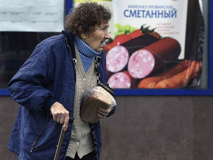 12 апреля, Ялта. Женщина с буханкой хлеба возле рекламного плаката