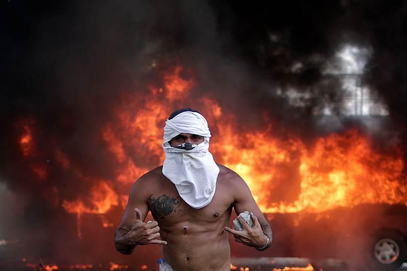 Протестующий против режима Николаса Мадуро на фоне горящего автобуса около авиабазы Ла Карлота в Каракасе