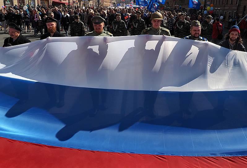 Участники первомайского шествия несут российский флаг