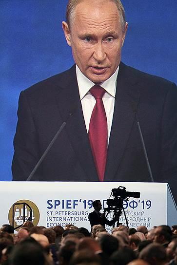 Президент России Владимир Путин (на экране) во время выступления на пленарном заседании