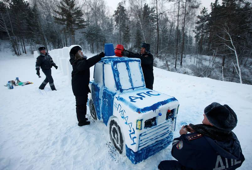 Сотрудники ГИБДД лепят патрульный автомобиль из снега