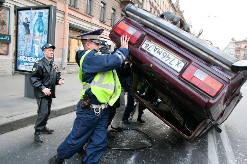 Гаишник помогает перевернуть автомобиль после ДТП