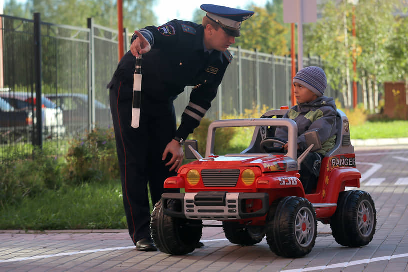 Гаишник учит ребенка правилам дорожного движения