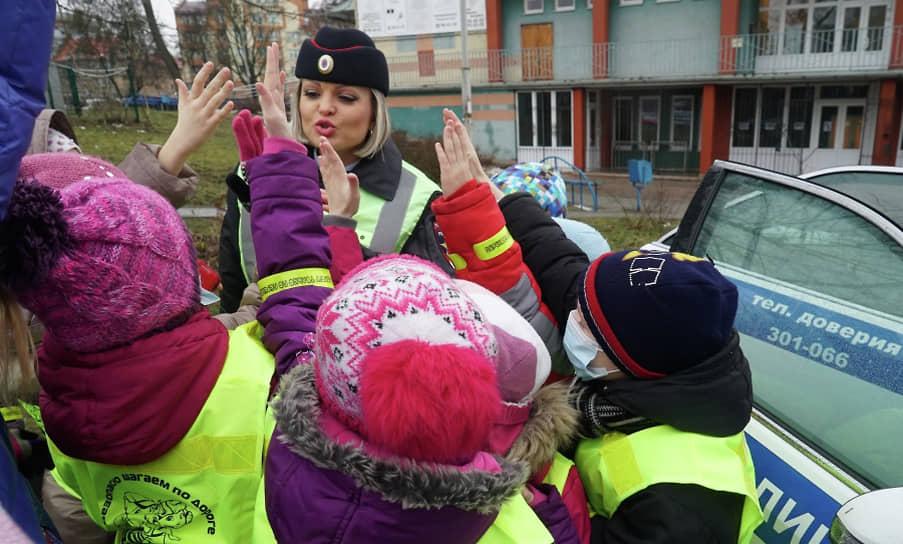 Госавтоинспектор и дети, изучающие правила дорожного движения