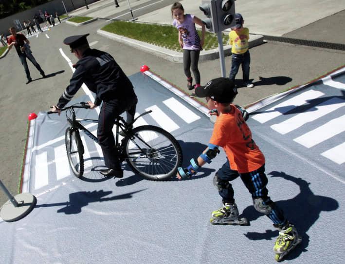 Сотрудник ДПС на велосипеде показывает, как правильно проезжать перекресток