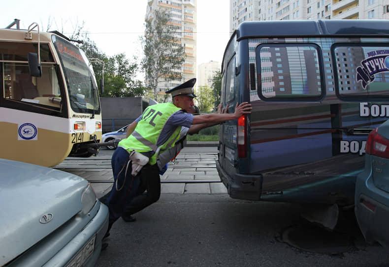 Сотрудник ДПС помогает убрать с дороги заглохшее транспортное средство