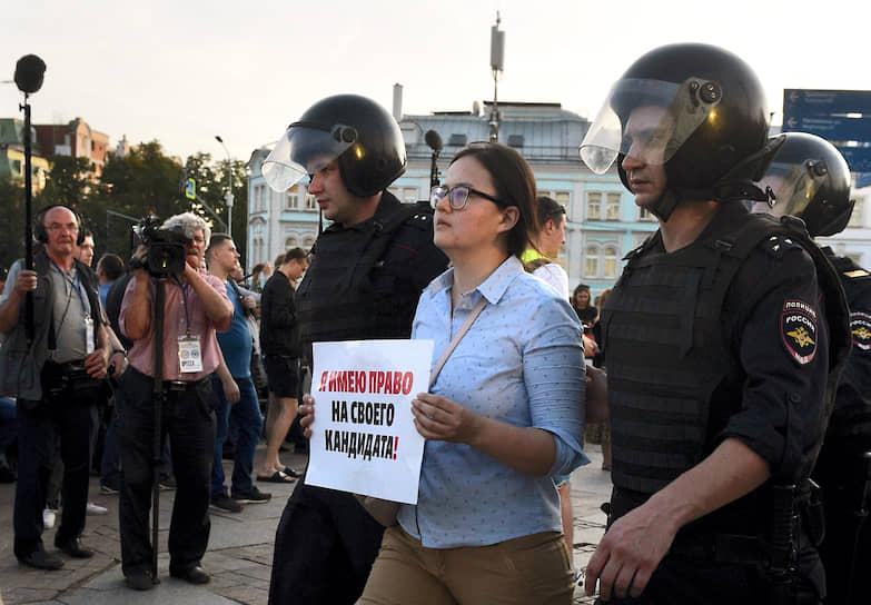 Сотрудники полиции во время задержания участницы акции